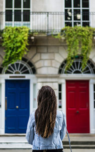 a woman choosing between a red door and a blue door